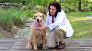 Integrative veterinarian Dr. Buzby kneeling beside dog that is wearing green ToeGrips for Dogs